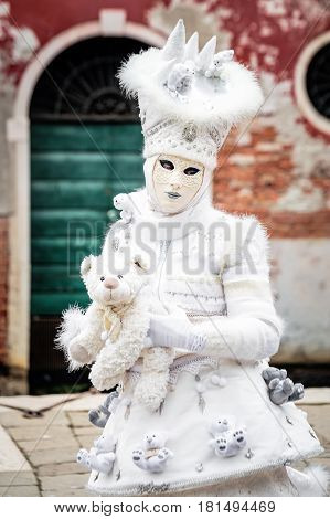 Snow white carnaval mask standing in front red wall background with iron green gate holding toy bear, Venice, Italy.