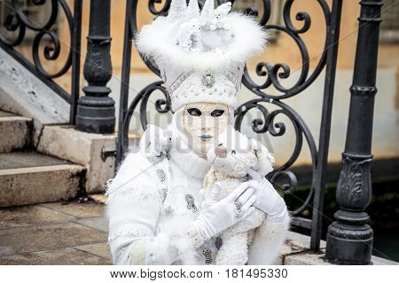 Venice white carnaval mask sitting with toy bear,Italy.