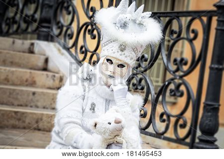 Venice white carnaval mask sitting with toy bear, Italy.