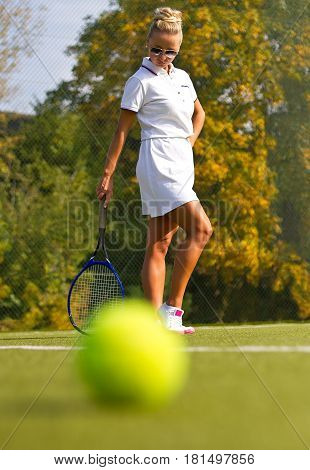 Tennis Ball On The Tennis Court With The Player In The Background