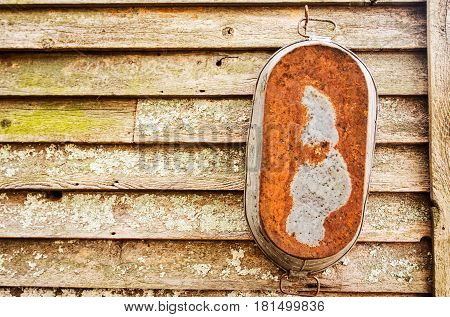 A rectangular old fashioned rusted metal wash tub hanging from a hook on exterior weathered wood board wall