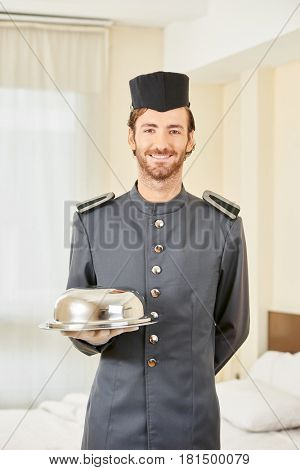 Page in hotel serving food with cloche in hotel room