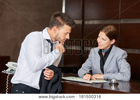 Receptionist in hotel giving advice to guest with a city map