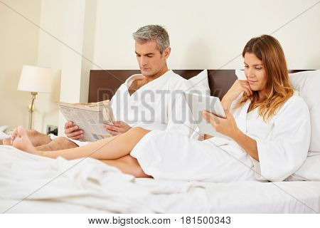 Couple reading newspaper and ebook in bed in a hotel room