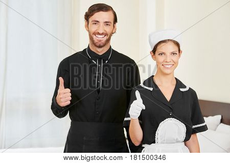 Hotel clerk and maid holding thumbs up as service team in hotel room