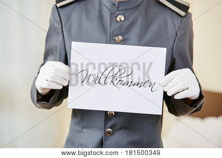 Hotel clerk holding German sign saying