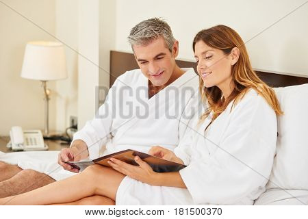 Couple in hotel room reading room service menu together in bed