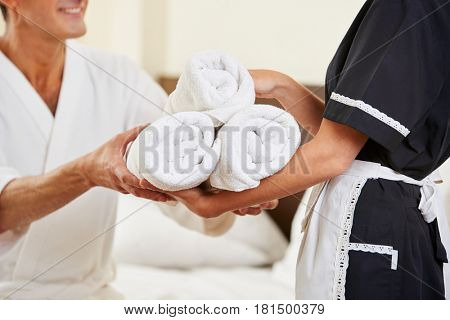 Maid bringing fresh towels during housekeeping in hotel room