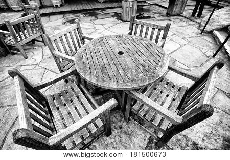 A round wooden table with four chairs outdoors on a stone tiled floor patio in black and white