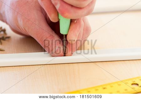 A Man Makes Holes With An Awl
