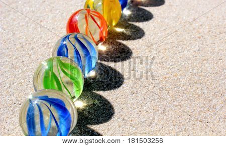 Colorful glass marbles on sand close up image