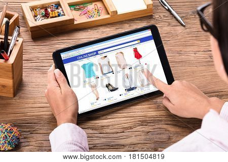 Close-up Of A Businesswoman Shopping Online Through Digital Tablet On Wooden Desk