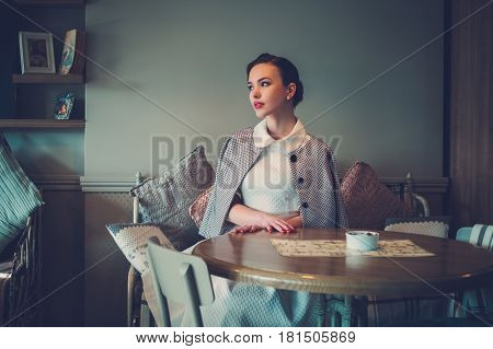 Elegant young lady alone in a cafe.