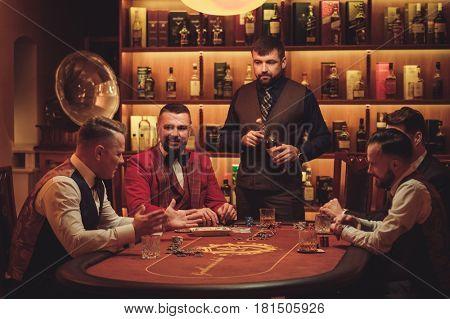 Group of men playing poker in gentlemen's club