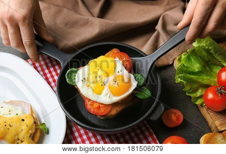 Woman serving egg Benedict for breakfast on table
