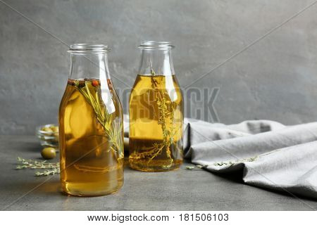 Olive oil with herbs on dark texture background