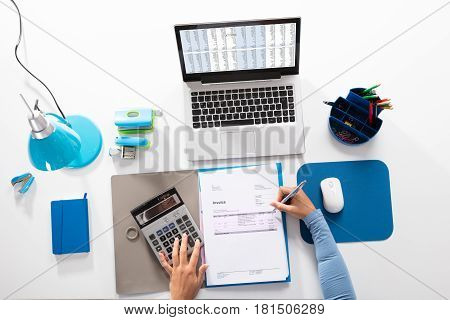 View Of A Businesswoman Calculating Invoice With Calculator On Desk At Workplace