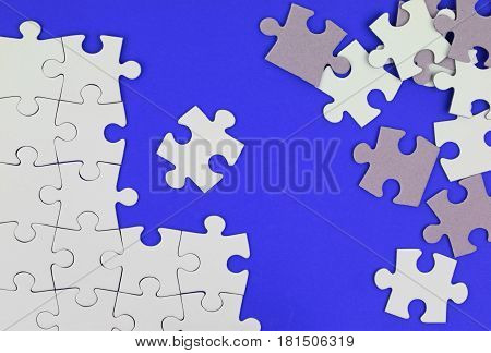 Puzzle pieces on blue background close up image