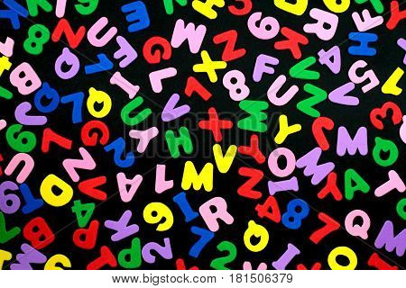 Colorful letters and numbers on black background.