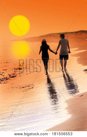 Young woman and man in love walking hand in hand on beach with beautiful sunset