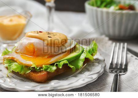 Tasty egg Benedict on plate, closeup