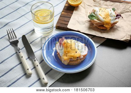 Breakfast with tasty eggs Benedict on table