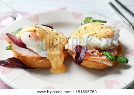 Tasty eggs Benedict on plate, closeup