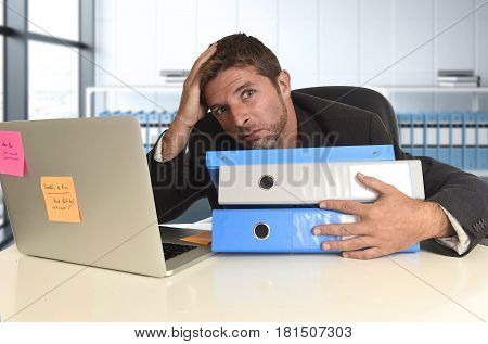 tired and frustrated businessman desperate face expression suffering stress at office computer desk holding paperwork folders overwhelmed at modern office in business financial district