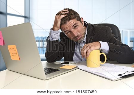 tired and frustrated businessman desperate face suffering stress and headache at computer desk busy with paperwork overwhelmed and stressed at modern office business financial district