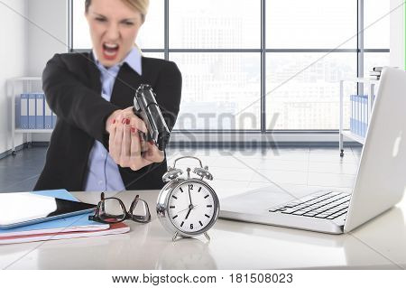 young attractive businesswoman furious and angry working with computer laptop pointing gun to alarm clock in out of time long hours of work and project deadline stress