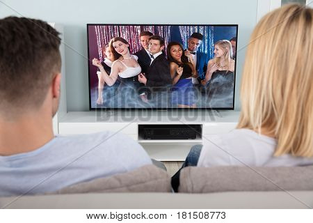 Rear View Of A Couple Watching The Young People Dancing In Television