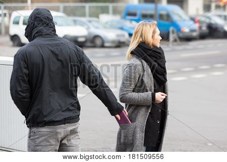 Man In A Hood Stealing Purse From Woman's Coat Pocket On Street