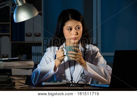 Woman Doctor Working At Night Drinking Coffee