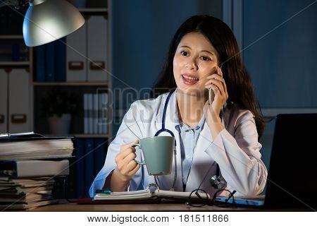 Female Doctor Drinking Coffee And Making Call