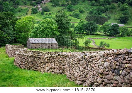 Stone Wall And A House In The Lake District, England