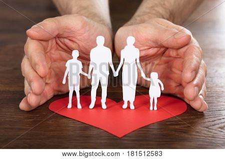 Person Hand Protecting Family Paper Cut With Red Heart On Wooden Desk