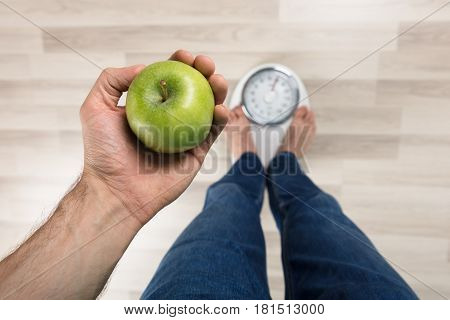 High Angle View Of A Person Measuring Weight While Holding Apple On Weighing Machine