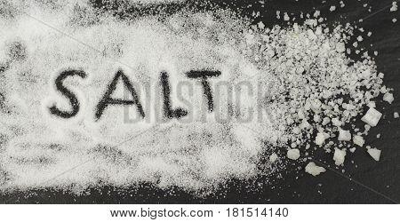 Thin salt and rock salt on black stone background.