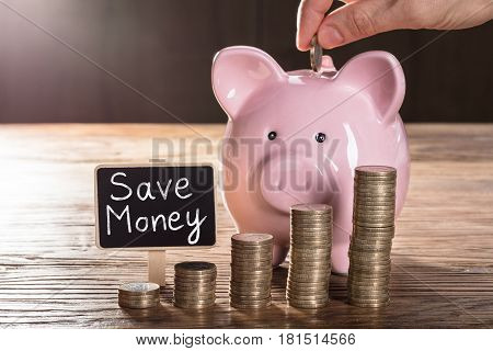 Person Inserting Coin In Piggybank With Coin Stacks On Wooden Table Showing Save Money Concept