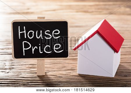 Text House Price Written On Small Blackboard With A House Model On Wooden Table