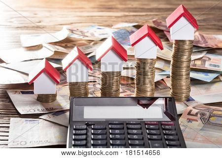 Miniature Houses Resting On Increasing Coin Stack With Calculator On Euro Notes