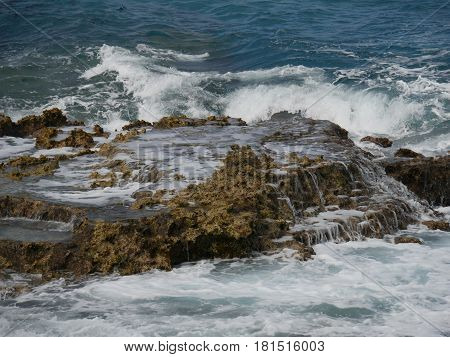 Crashing waves on rocks foams of water crash against the sharp rocks provide a beautiful view