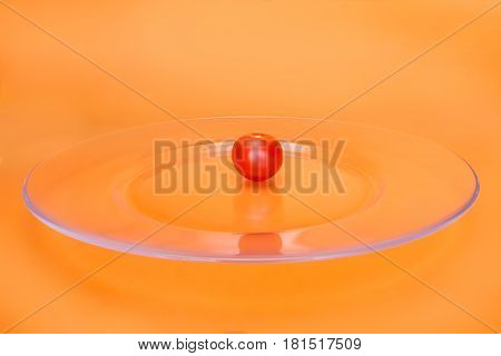 Small red cherry tomato on transparent glass plate. On abstract orange background selective focus
