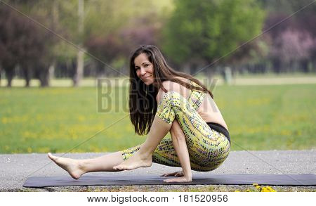 Young woman doing yoga in morning park. Eka hasta bhujasana, elephant's trunk pose.  Healthy lifestyle outdoor conception.