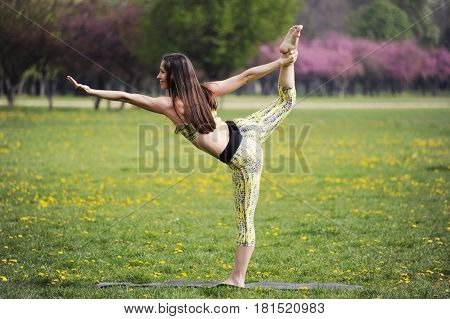 Young woman doing yoga in morning park. Utthita ardha dhanurasana, standing half bow pose.  Healthy lifestyle outdoor conception.