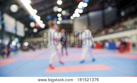 Teenagers karatekas fight on karate competitions, de-focused sport background, wide angle