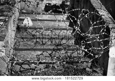 An abandoned staircase covered with barbed wire. Abandoned place and forbidden area theme