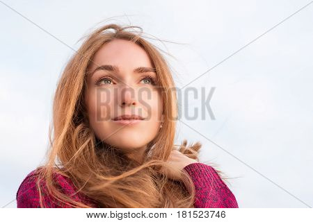 Serene beautiful woman with long hair fluttering in the wind. Outdoor portrait. Looking up at the distance low point view