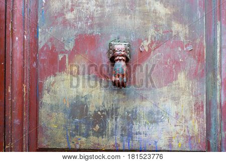 Old paint smeared door with knocker in shape of human hand in center