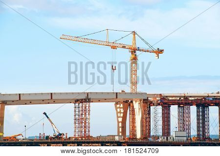 Bridge under construction. Tail crane elevated road and construction frame